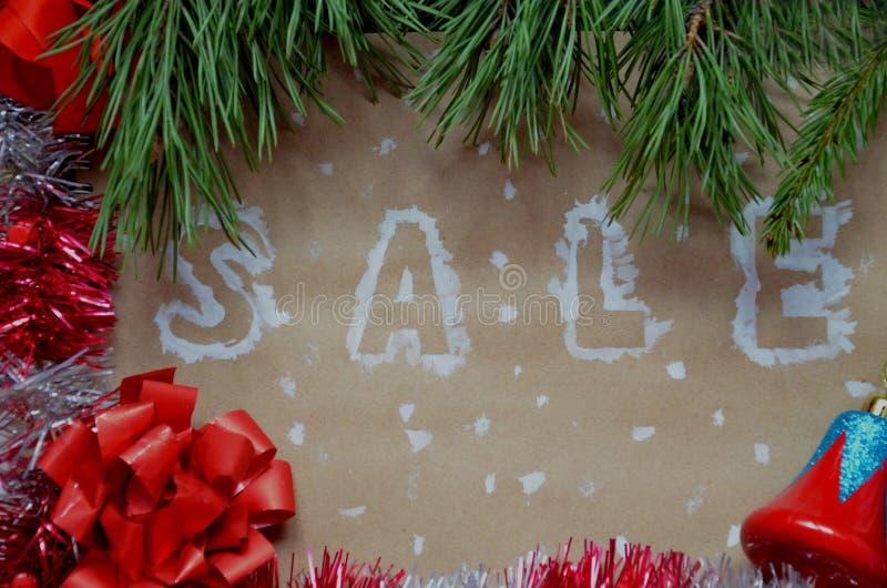 En inskrift av en försäljning på en julbakgrund nytt år för garnering på kraft papper Julaskar i snö med royaltyfri foto