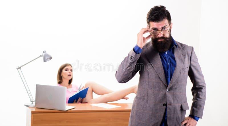 En intellektuell blick av hipsteren Hipster som fixar hans exponeringsglas medan sexig kvinna som arbetar i bakgrund Skäggig hip arkivbild