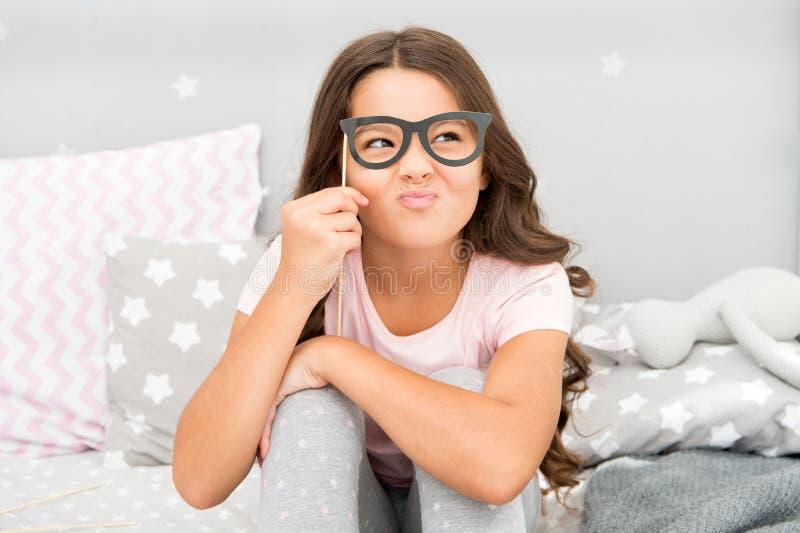 En intellektuell blick Lycklig liten flicka Den lilla flickahållen fejkar exponeringsglas på framsida lycklig barndom Lyckliga ba royaltyfria bilder