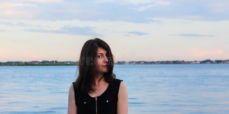 En intressant flicka i en svart dräkt på stranden ser kameran arkivfoto