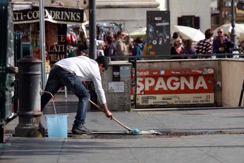 En invandrare gör ren vägen arkivbild