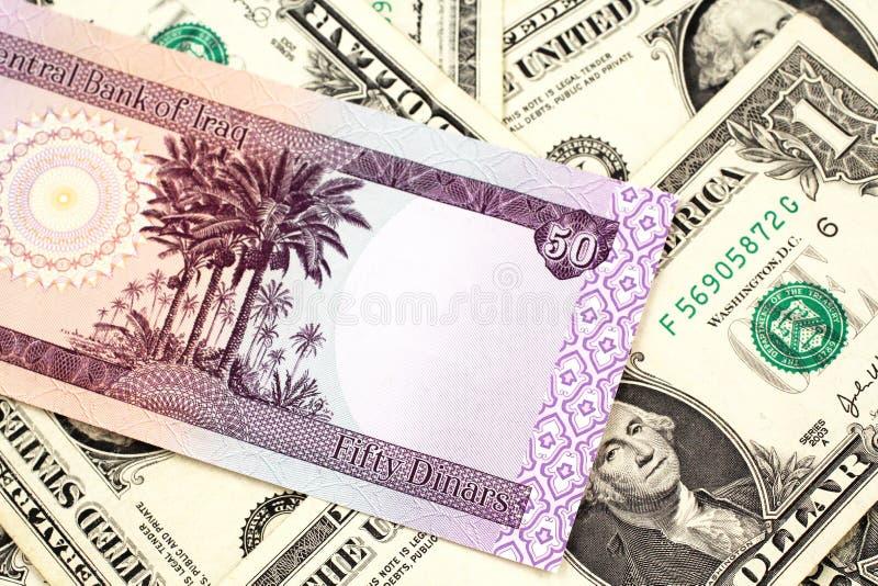 En irakisk femtio dinar sedel med amerikanen en dollar räkningar royaltyfri foto