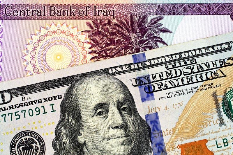 En irakisk femtio dinar sedel med en amerikansk hundra dollarräkning royaltyfria bilder