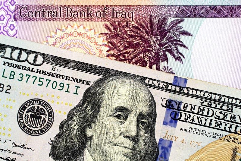 En irakisk femtio dinar sedel med en amerikansk hundra dollarräkning arkivfoto