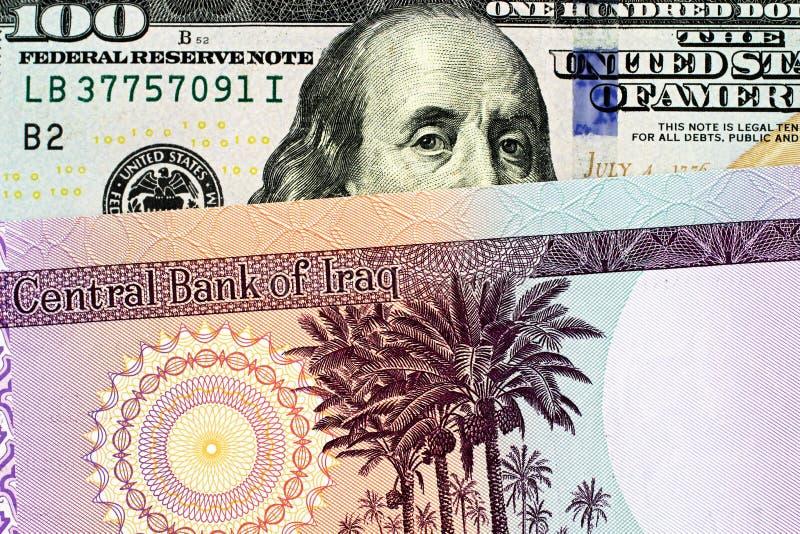 En irakisk femtio dinar sedel med en amerikansk hundra dollarräkning royaltyfria foton
