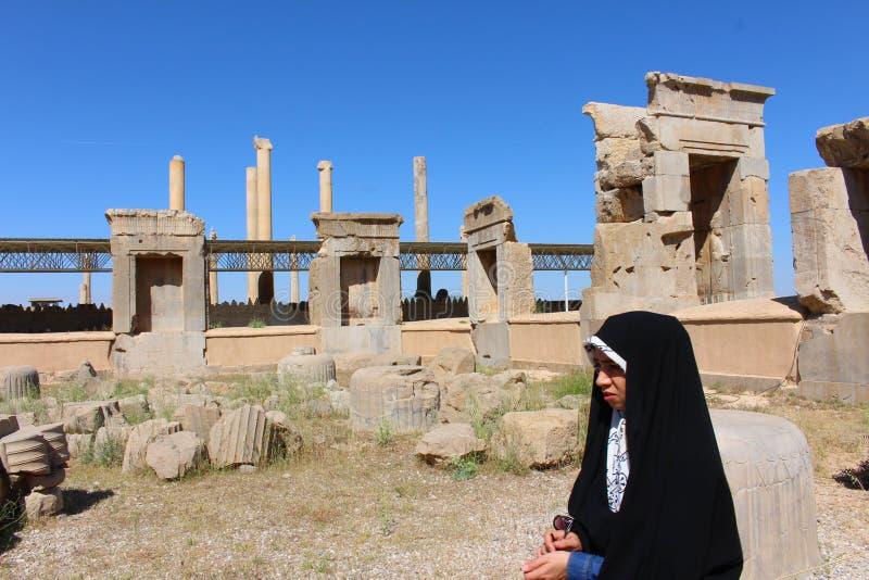 En iransk flicka av fördärvar framme av Persepolis arkivfoto
