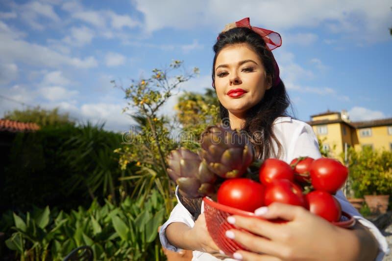 En italiensk kvinna, en hemmafru, samlar grönsaker för matställe i en hem- trädgård royaltyfria bilder