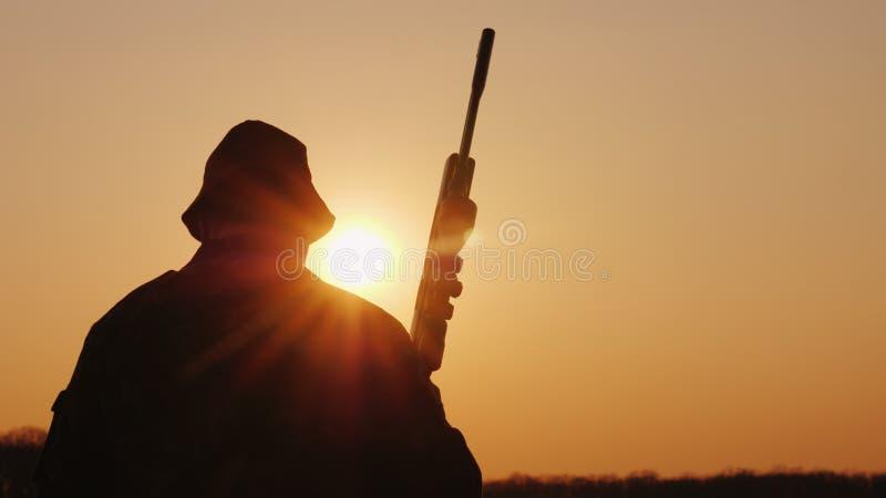 En jägare med ett vapen går framåtriktat över fältet in mot inställningssolen Hobby f?r m?n arkivbild