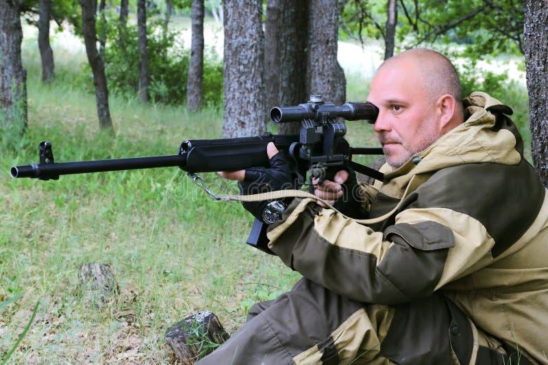 En jägareman med ett skjutvapen sitter i en skog under sikta för träd arkivfoto