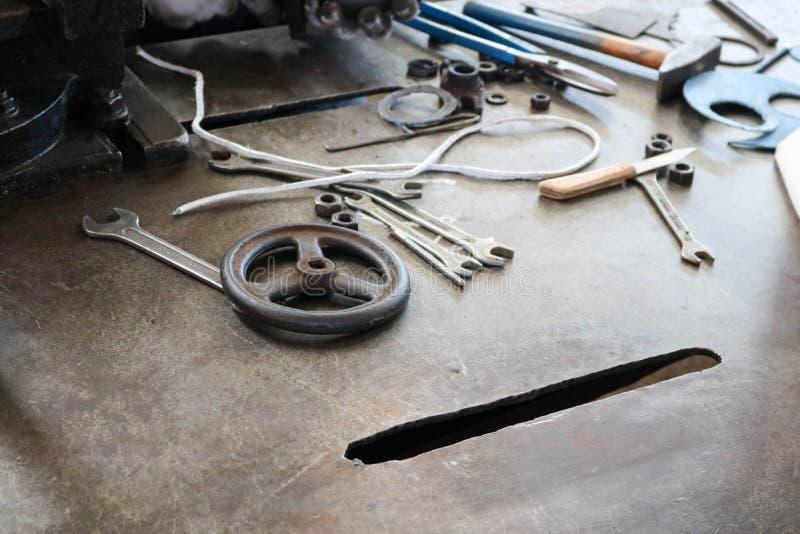 En järntabell med ett metallarbetehjälpmedel, skiftnycklar, hammare, skruvmejslar, pojkar, knivar, ventiler i fabriken, en fabrik arkivbild