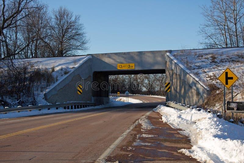En järnvägbro över en lantlig huvudväg arkivbilder