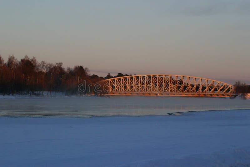 En järnvägsbro i aftonsol på en vinterdag royaltyfri bild