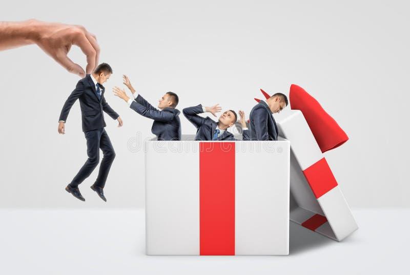 En jätte- hand som rymmer en mycket liten affärsman nära en ask full av tre andra män inom en stor gåvaask royaltyfri foto