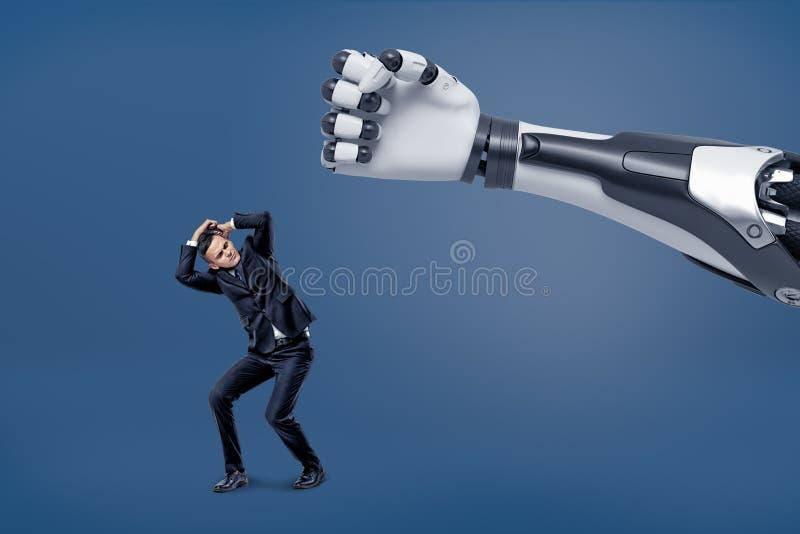 En jätte- robotic hand är klar att slå en mycket liten förskräckt affärsman med en näve royaltyfri bild