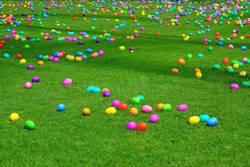 En jakt för påskägg med plast- ägg på en grön gräsmatta