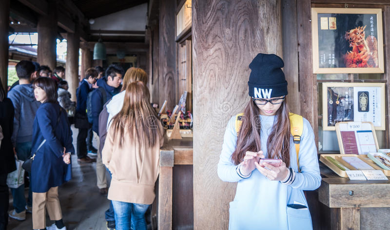 En japansk tonåring spelar med hennes mobiltelefon i en tempel fotografering för bildbyråer