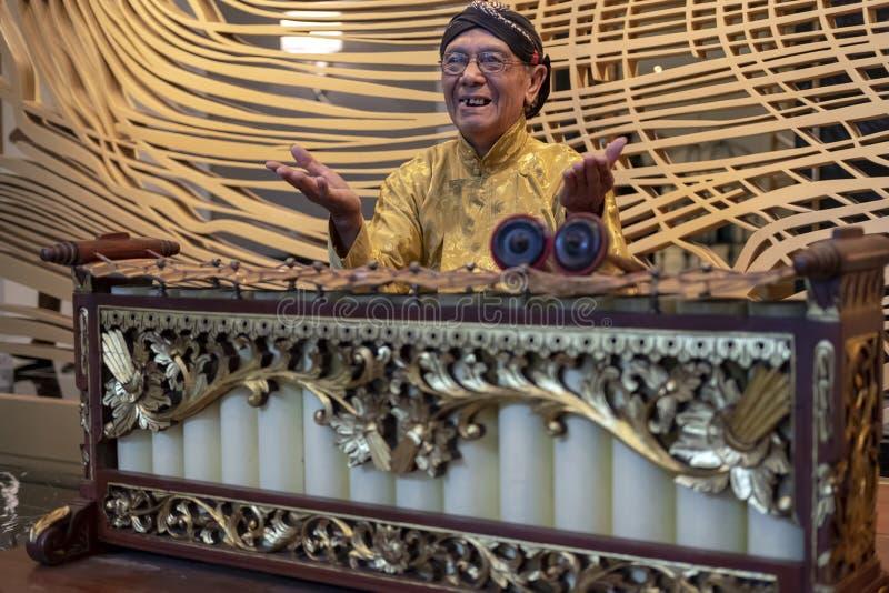 En Javanese man som spelar slenthem, ett Javanese traditionellt musikinstrument arkivbilder