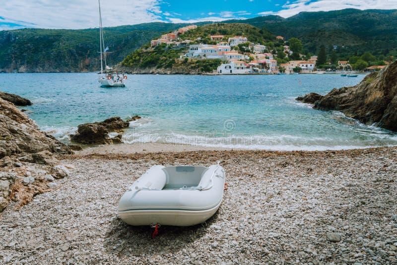 En jolle på den lilla dolde stranden i den Assos byn Vit yacht i den Assos fjärden Kefalonia Grekland royaltyfri foto