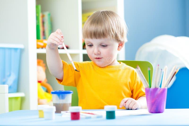 En jong geitje thuis of kleuterschool of playschool die spelen schilderen royalty-vrije stock afbeelding