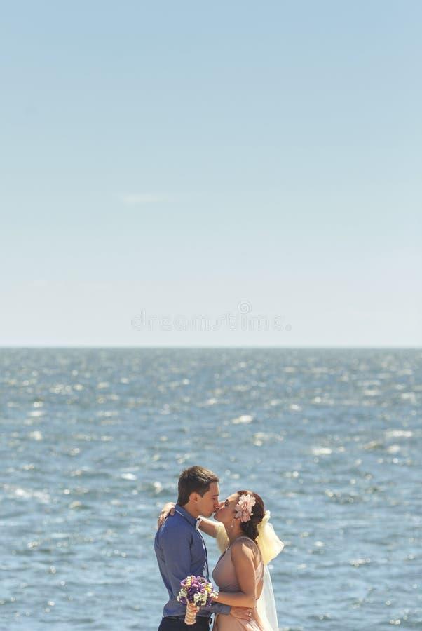 En jonggehuwden die omhelzen kussen royalty-vrije stock foto's