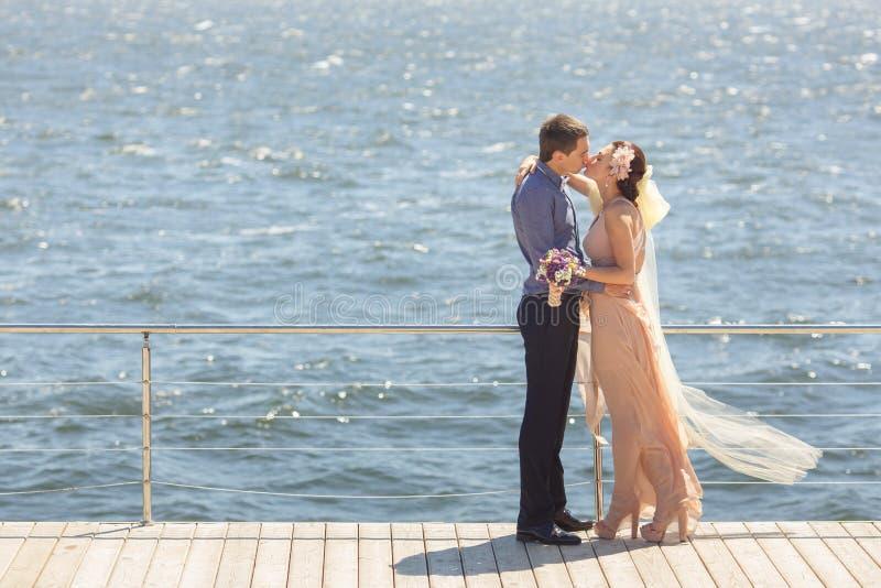 En jonggehuwden die omhelzen kussen stock afbeeldingen