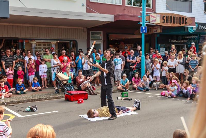 En jonglör i gatan med en modig volontär royaltyfria bilder