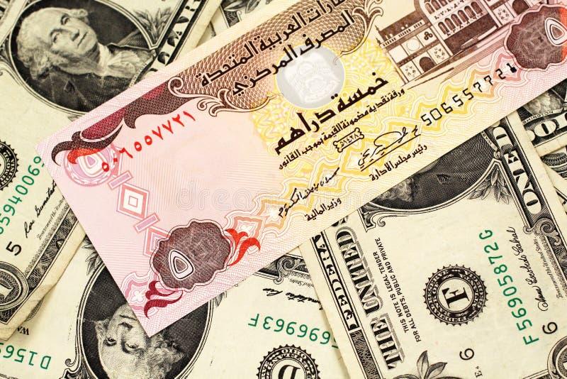 En en jordansk dinar på en bakgrund av amerikanen en dollar räkningar arkivfoto