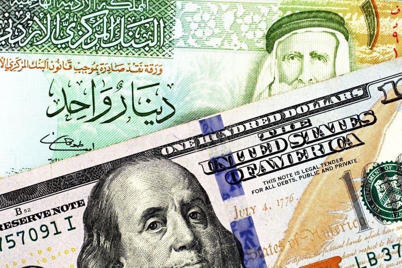 En jordansk en dinarsedel med en amerikansk hundra dollarräkning arkivbild
