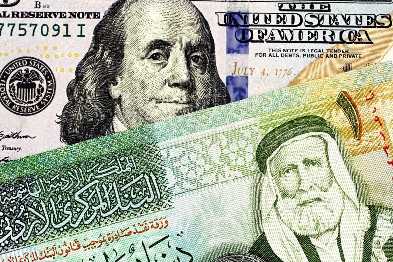 En jordansk en dinarsedel med en amerikansk hundra dollarräkning fotografering för bildbyråer