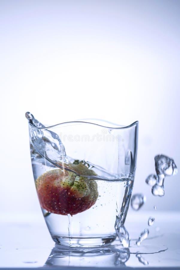 En jordgubbe som plaskar upp som vatten från ett exponeringsglas på en vit bakgrund, slut är abstrakt royaltyfri fotografi