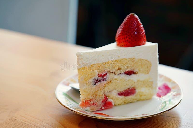 En jordgubbeshortcake som överträffas med en stor ny jordgubbe som förläggas i den vita plattan och på trätabellen med kopierings fotografering för bildbyråer