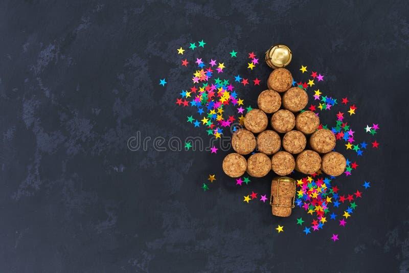 En julgran som göras från använda champagneflaskkorkar med färgrika konfettier på svart bakgrund med kopieringsutrymme royaltyfri fotografi