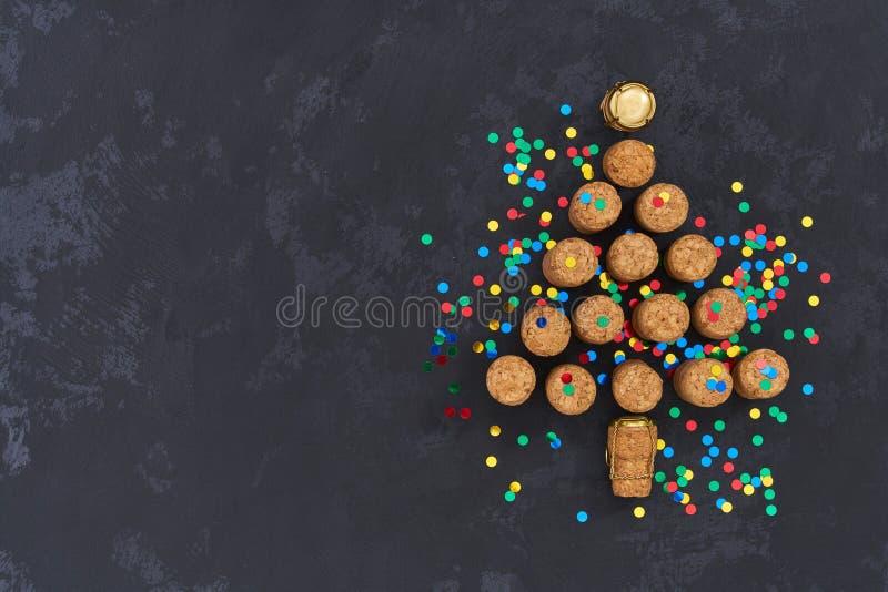 En julgran som göras från använda champagneflaskkorkar med färgrika konfettier på svart bakgrund med kopieringsutrymme arkivfoton