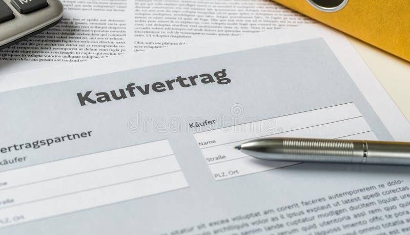 En köpöverenskommelse med en penna på ett skrivbord - Kaufvertrag tysk royaltyfria foton