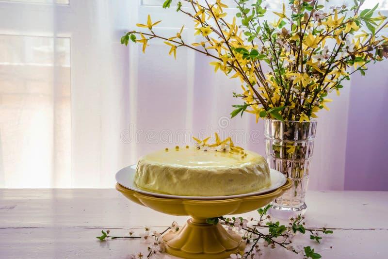 En kaka med citronen och kokosnöten på ett gult magasin och en bukett av våren blommar royaltyfri foto