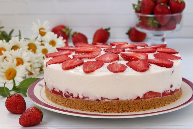 En kaka med jordgubbar utan bakning, med en grund av kex, förläggas horisontellt på en platta på ett vitt fotografering för bildbyråer