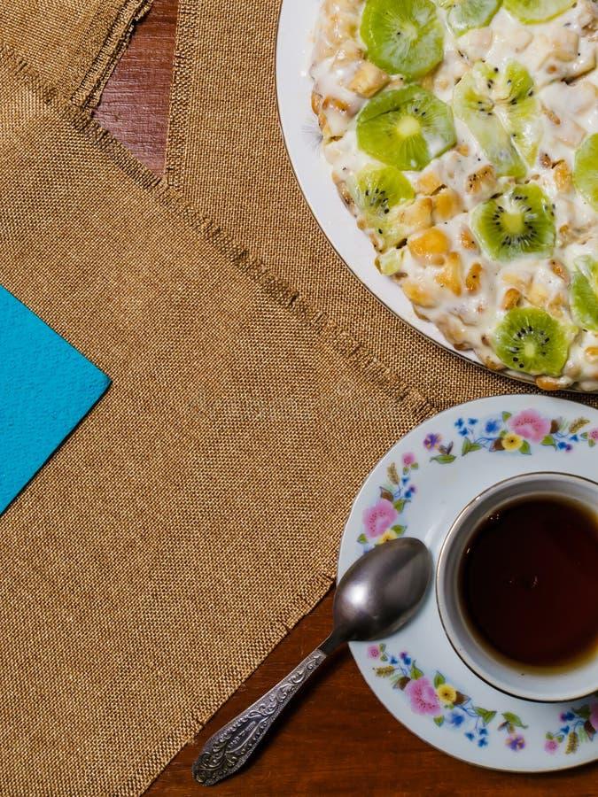 En kaka som göras från kex som dekoreras med kiwiskivor, lögner i en vit platta bredvid ett tefat och en kopp av svart te på ruti fotografering för bildbyråer