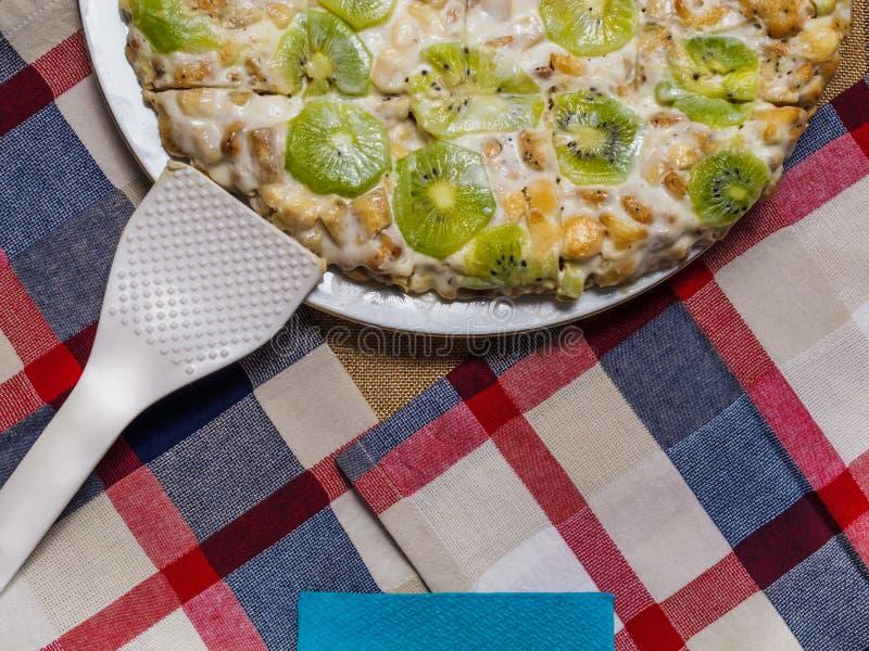 En kaka som göras från kex som dekoreras med kiwiskivor, lögner på en vit platta fotografering för bildbyråer