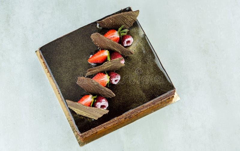 En kaka som gjordes av svart choklad, dekorerade med hallon arkivfoto