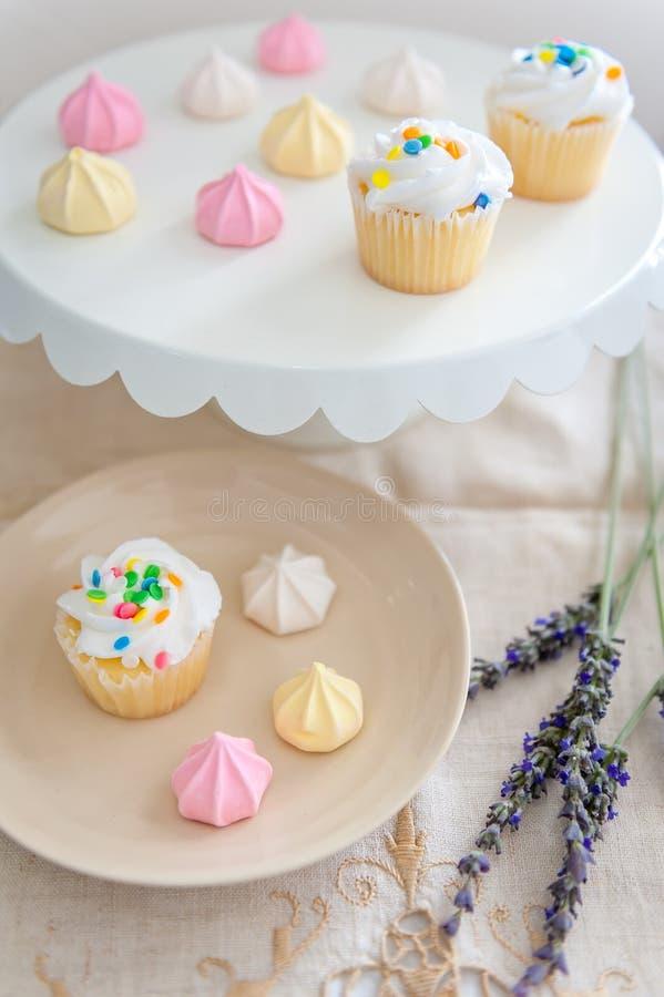 En kakaplatta och efterrättplattan som fylldes med konfettier, strilade muffin och pastellfärgade kulöra marängtuggakakor royaltyfri foto