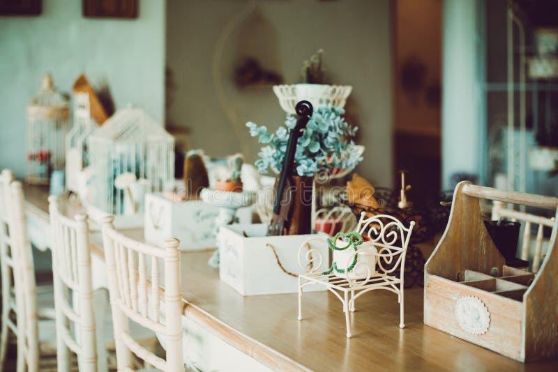 En kaktus i liten kruka på liten stol och de är på trätabellen i coffee shop arkivfoton