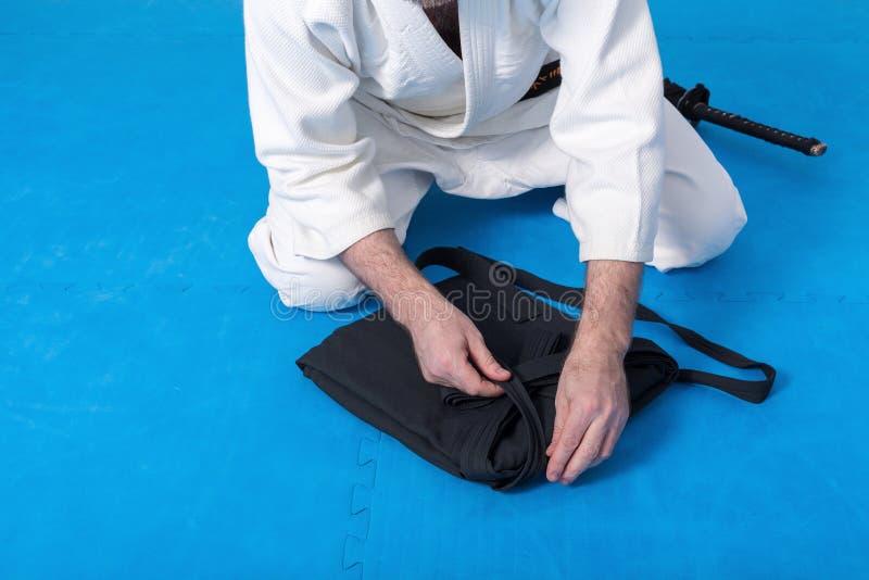 En kampsportförlage med det svarta bältet som viker hans hakama royaltyfri foto