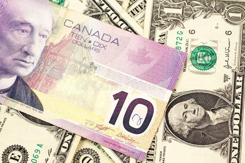 En kanadensisk räkning för dollar tio på en bakgrund av dollarräkningar arkivfoto