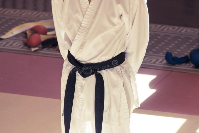 En karateinstruktör i en kimono med ett svart bälte är i utbildning på idrottshallen royaltyfri bild