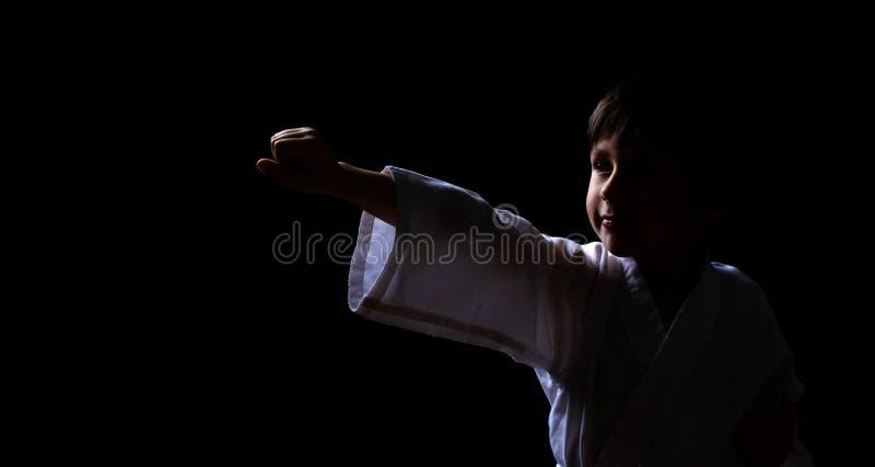 En karatepojke i den vita kimonot som poserar på mörk bakgrund Barnet som är klart för kampsporter, slåss Unge som slåss på Aikid royaltyfria bilder