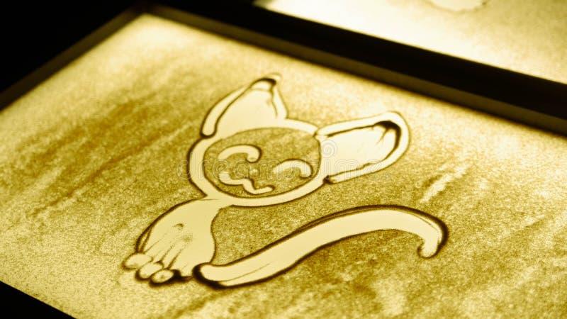 En katt som dras med en sand på skärmen royaltyfria foton