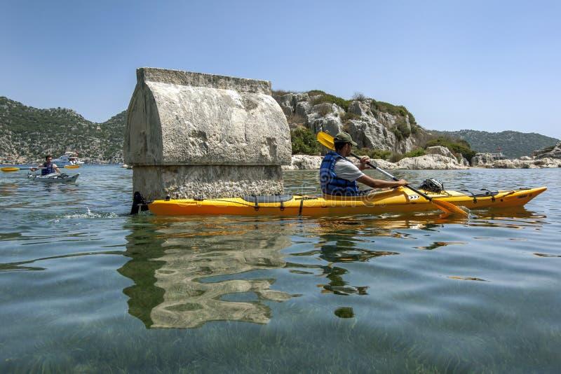 En kayaker paddlar forntid en av de sjunkna Lycian gravvalven på den forntida staden av Simena i Turkiet arkivfoton