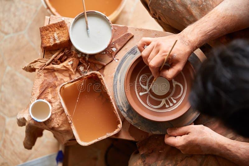 En keramiker målar en leraplatta i en vit i seminariet, den bästa sikten, närbilden, selektiv fokus arkivfoto