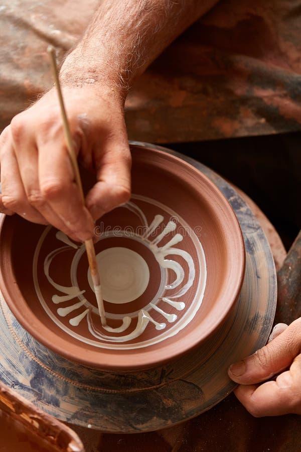 En keramiker målar en leraplatta i en vit i seminariet, den bästa sikten, närbilden, selektiv fokus royaltyfri foto