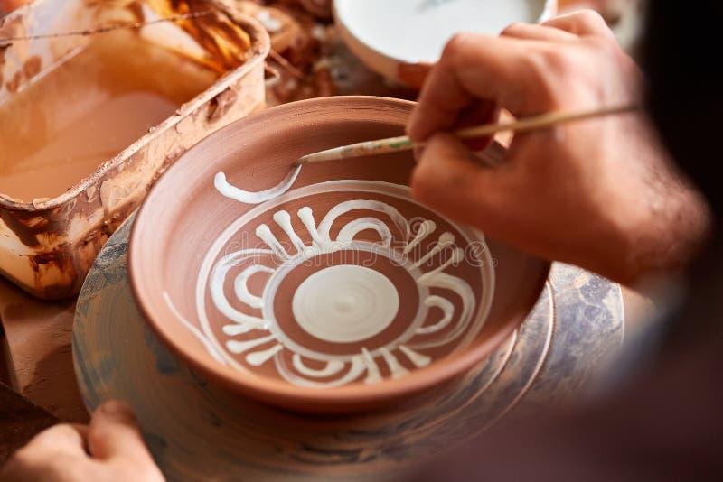 En keramiker målar en leraplatta i en vit i seminariet, den bästa sikten, närbilden, selektiv fokus arkivbild